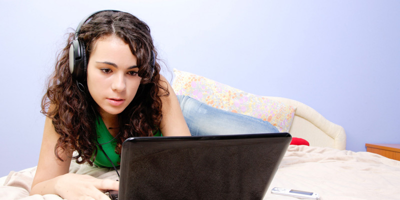 Teen girl in her bed looking on her laptop; Shutterstock ID 61412050; PO: The Huffington Post; Job: The Huffington Post; Client: The Huffington Post; Other: The Huffington Post